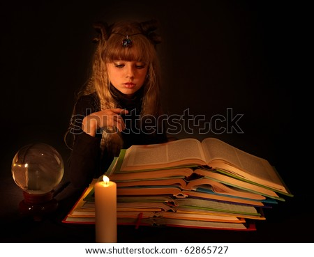 Child reading magic book at candle. Crystal ball on table.