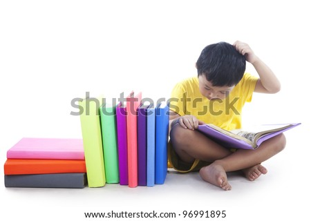 Child reading the books and scratching his head, shot in studio isolated on white background