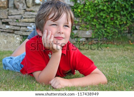 stock-photo-child-relaxing-on-green-grass-looking-thoughtful-117438949.jpg