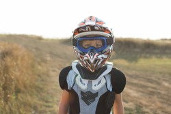 Child rider on motorcycle. Small biker dressed in a protective suit and helmet. The kid is engaged in motocross