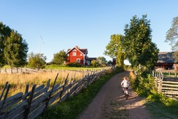 Child riding a bicycle along a small farm lane in rural Sweden pedaling towards a traditional red painted timber house