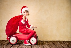 Child riding in red car. Kid holding Christmas bag. Xmas holiday concept