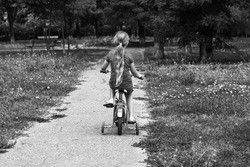 Child riding on bicycle. Blonde smiling girl on bike on asphalt road in summer. Active lifestyle leisure, physical training on sports stadium. Happy kid bicyclist. Black and white street photo.