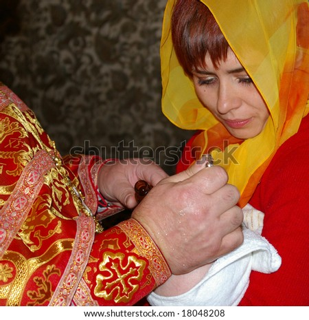 Child rite. Orthodoxy minister, godmother and baby.