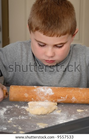 Child rolling out dough with rolling pin - stock photo