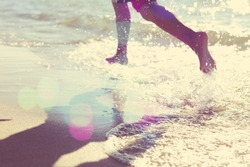Child running at the beach, runner has motion blur. Focus on sand