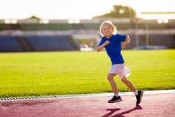 Child running in stadium. Kids run on outdoor track. Healthy sport activity for children. Little boy at athletics competition race. Young athlete in training. Runner exercising. Jogging for kid.