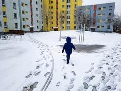 Child runs through the snow in Leherheide, Bremerhaven in Germany.
