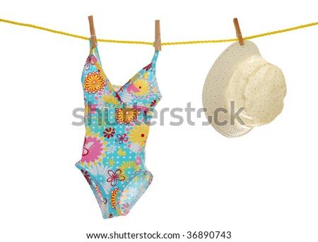 child's bathing suit and beach hat on clothes line