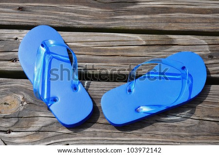 Child's blue flip flops sitting on a boardwalk
