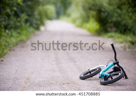 Child's bycycle lying on the road in the park. Balance bike for toddler.