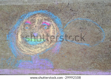 Child's chalk drawing of a smiling face with speech bubble on concrete.