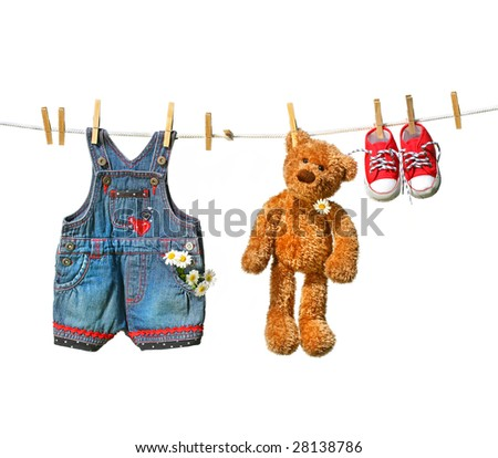 Child's clothes with teddy bear on clothesline on white - stock photo