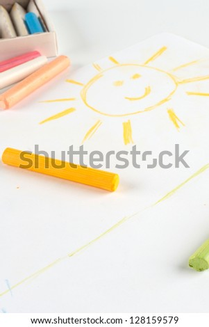 Child's drawing of a smiling sun. Done pastel on album sheet.