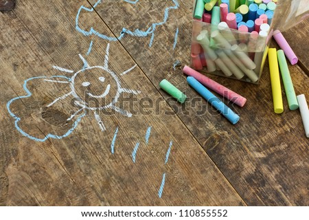 Child\'s drawings and colored chalk on wooden background