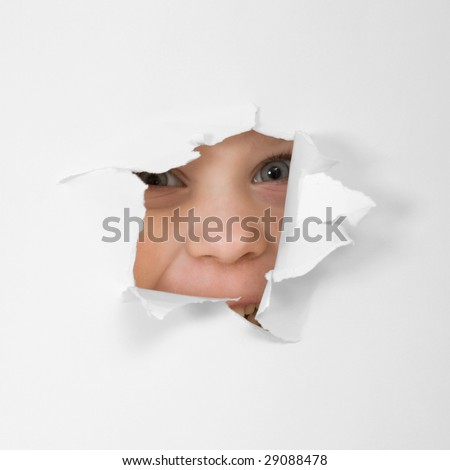 Child's eye looking through hole in sheet of paper