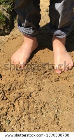 Child's feet glistening in the sand.