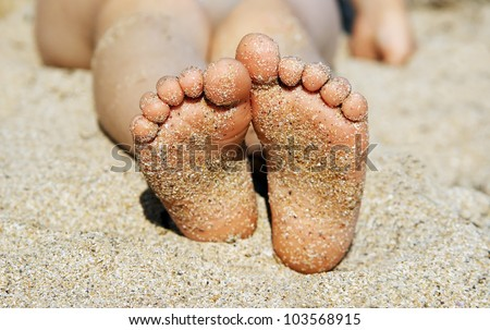 Child's feet in the sand close-up