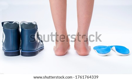 Child's feet, orthopedic shoes and insoles isolated on a white background. Valgus deformity of the feet. Treatment of flat feet. Medical shoes. Individual orthopedic insoles.
