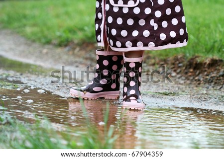 Child's feet playing in a mud puddle. Selective focus on little girl with extreme shallow DOF. Some blur on lower portion.