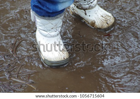 Child's feet stomping in a mud puddle. children's shoes in the mud. Little girl's  white boots in the mud