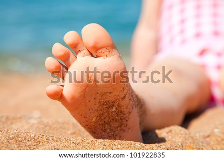child's foot is close to the sandy beach of the seaside resort