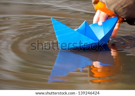 Child's hand and blue paper boat in water in spring ストックフォト ©