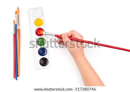 child's hand dips the brush in watercolor