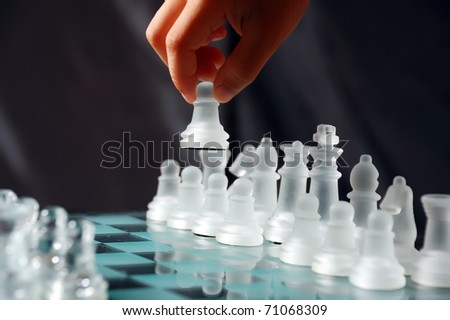child's hand doing first move with a pawn - stock photo