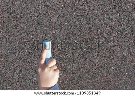 child's hand draws hearts, drawings chalk on asphalt #1109851349