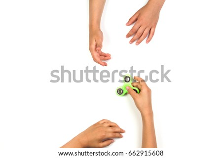 Child's hand giving fidget spinner to another child hands on white background. Top view