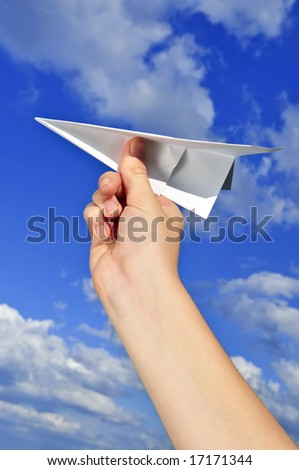 Child's hand holding a paper airplane on blue sky background