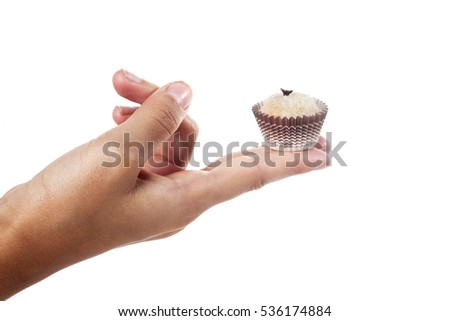 Child's hand holding a traditional candy from Brazil, a white brigadeiro. #536174884