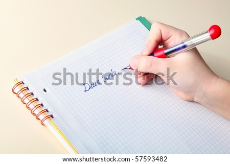 "Child's hand holding ink pen, while he writes a letter to Santa Claus in checkered workbook asking for Christmas' gift, ""Dear Santa,"" and copy space for your message."