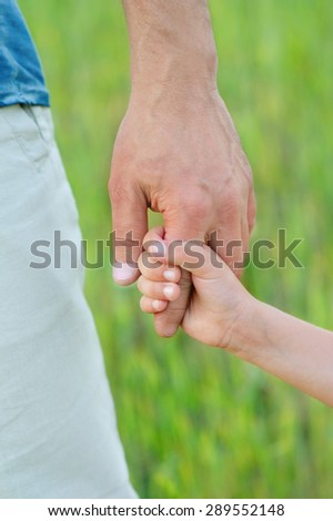 Child\'s hand holding on to a man\'s hand. Child\'s hand. Man\'s hand.