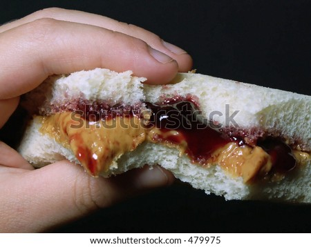 child's hand holding peanut butter & jelly sandwich - stock photo