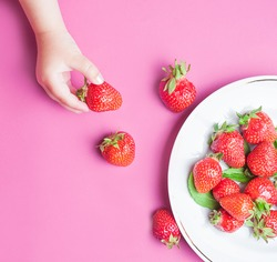 Child's hand holding strawberry on pink concrete background, plate of strawberries. Summer healthy eating concept. Top view, flat lay.