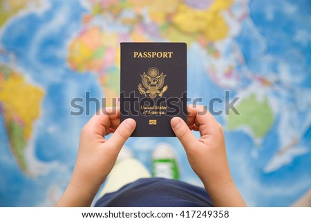 Child's hand holding US passport. Map background. Ready for traveling. Open world. #417249358