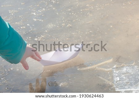Child's hand launches white paper boat into puddle of ice. Early spring mood concept, freedom. ストックフォト ©