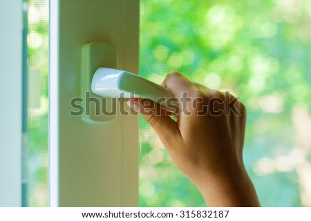 Child\'s hand opens a plastic window closeup