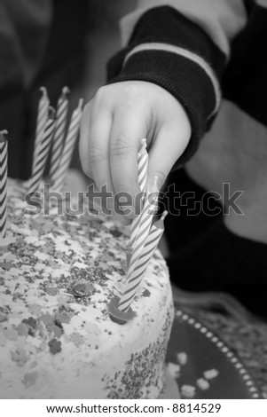 child\'s hand places candle on cake - black and white