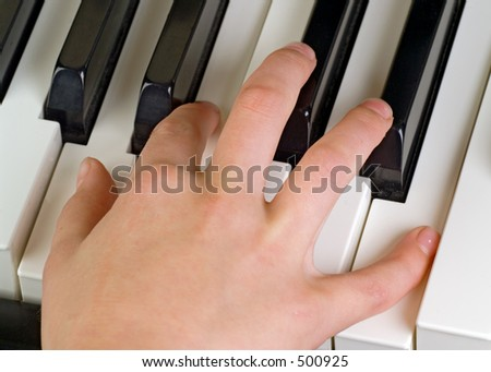 child's hand playing the piano