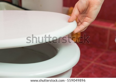 Child's hand puts the toilet seat #559049896