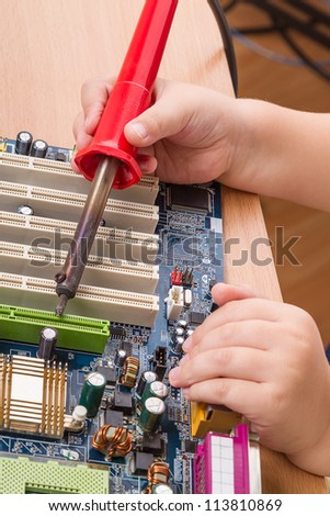 child 39 s hand with a soldering iron and a motherboard stock photo 113810869 shutterstock. Black Bedroom Furniture Sets. Home Design Ideas