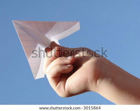 child's hand with paper plane