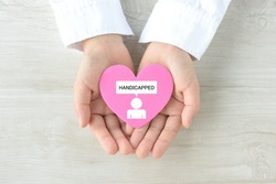 Child's hands covering heart object with handicapped person pictogram