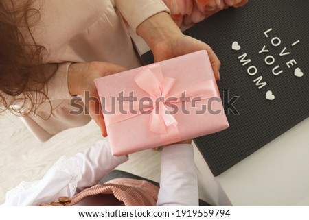 Child's hands hold beautiful pink gift box with ribbon. Pink tulip flower and sign i love you mom in background. Top view, close-up. Preparing for the holidays.
