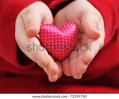 Child's hands hold heart from a pink satin with pattern - stock photo