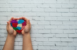Child's hands holding a multicolored heart on white background with place for your text. World autism awareness day concept.