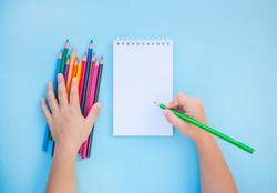 Child's hands holding colorful pencils and a notebook on blue background with copyspace. Flat lay style. Back to school concept.